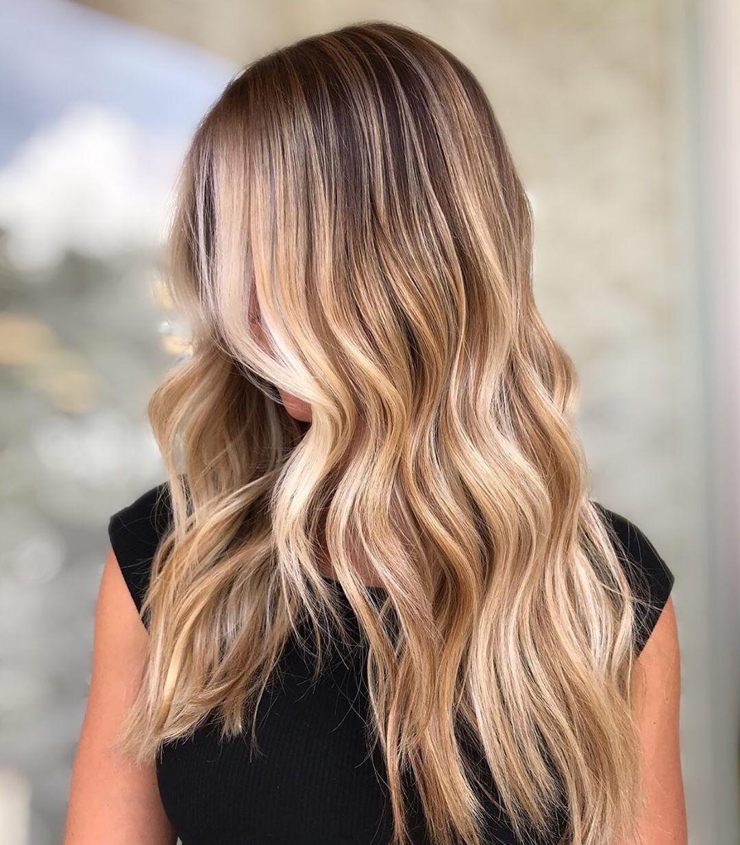 Femme aux longs cheveux ondulés blond miel méché