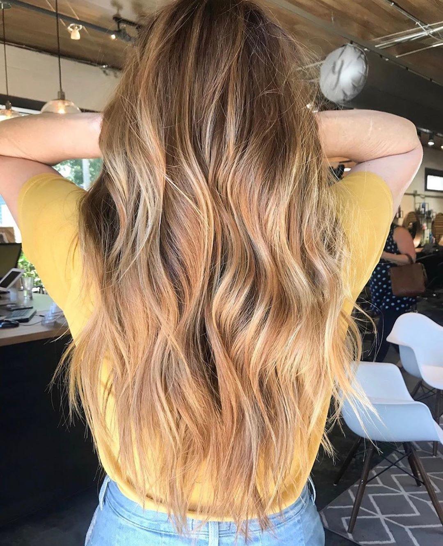 Femme avec de longs cheveux balayés blond miel ondulés.