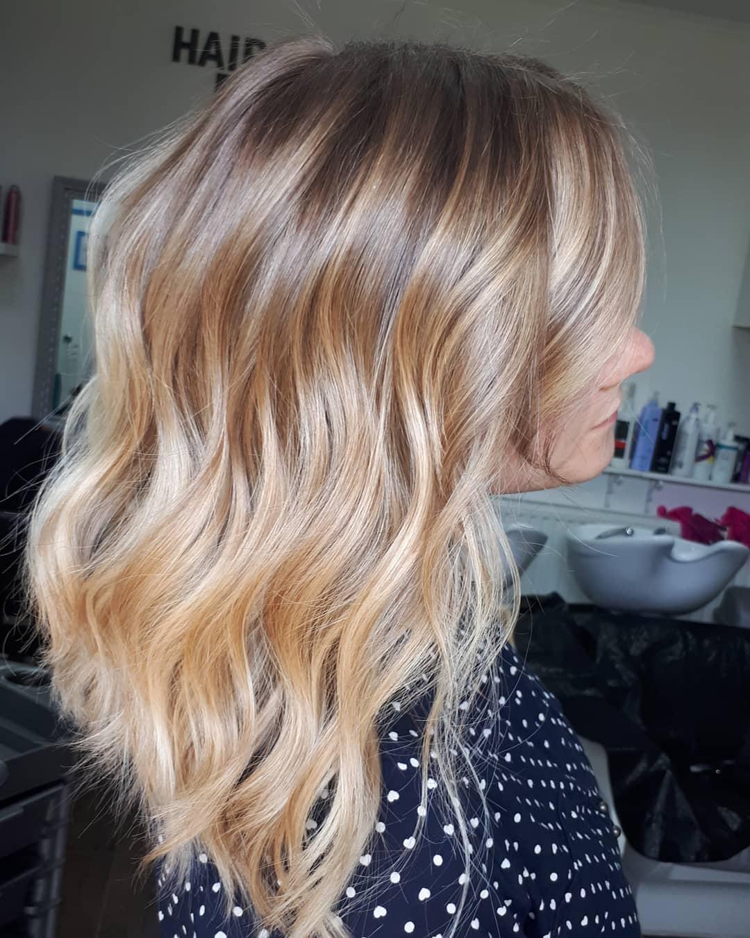 Femme avec des cheveux mi-longs ondulés de couleur beige miel.