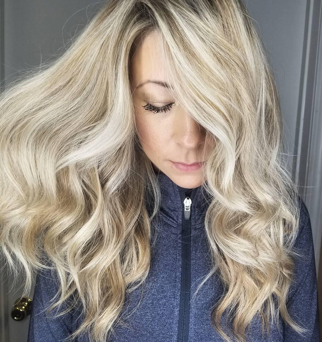 Femme avec des cheveux blond miel clair bouclés avec une raie sur le côté.