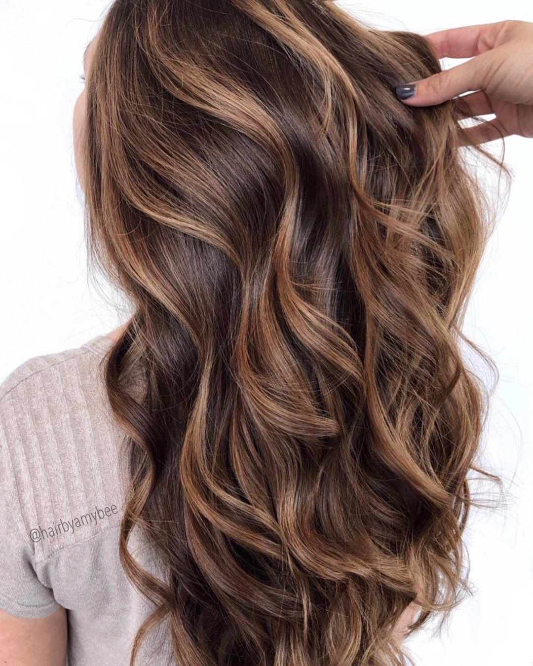 Femme aux longs cheveux bruns foncés bouclés avec des reflets miel.