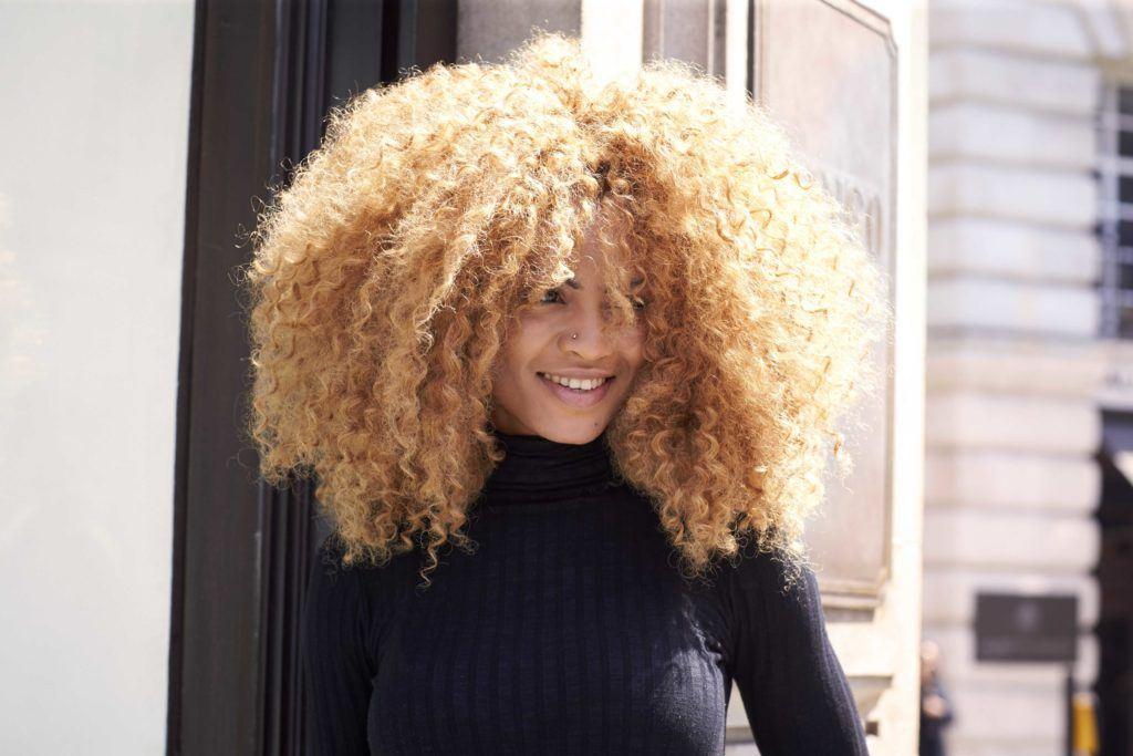 vue de face d'une femme aux grands cheveux bouclés dans une nuance de couleur blonde miel cuivré