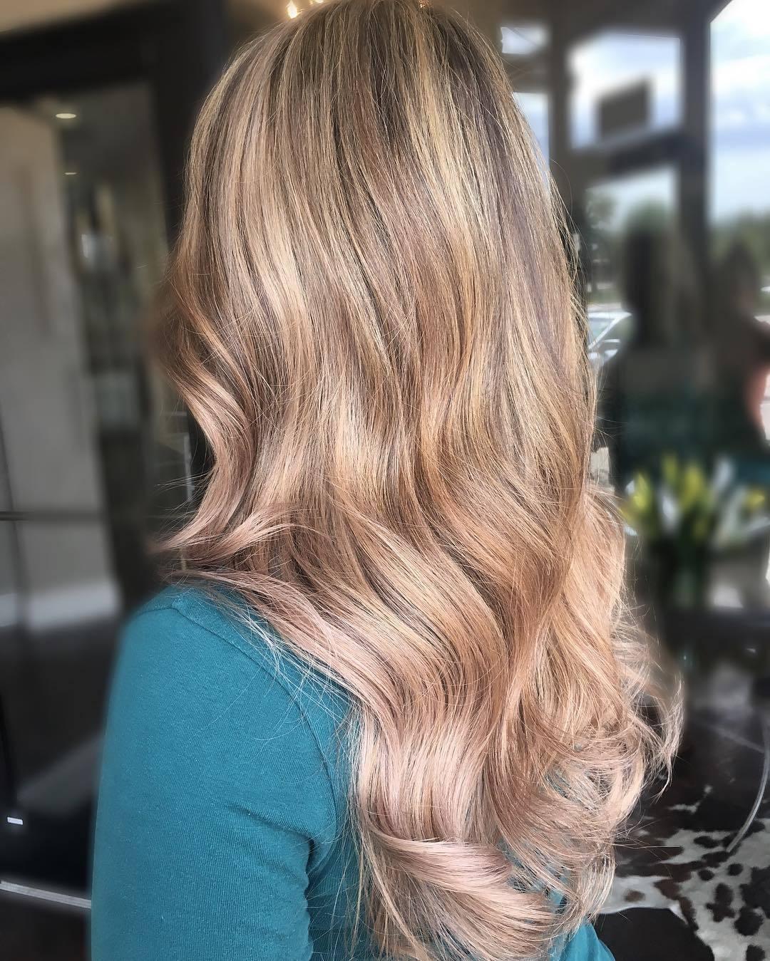 Femme avec de longs cheveux ondulés blond miel cendré.