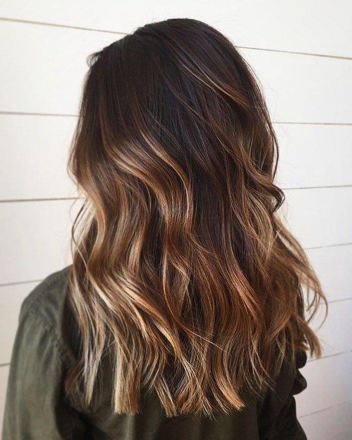 Femme avec des cheveux foncés mi-longs et ondulés avec des reflets miel.