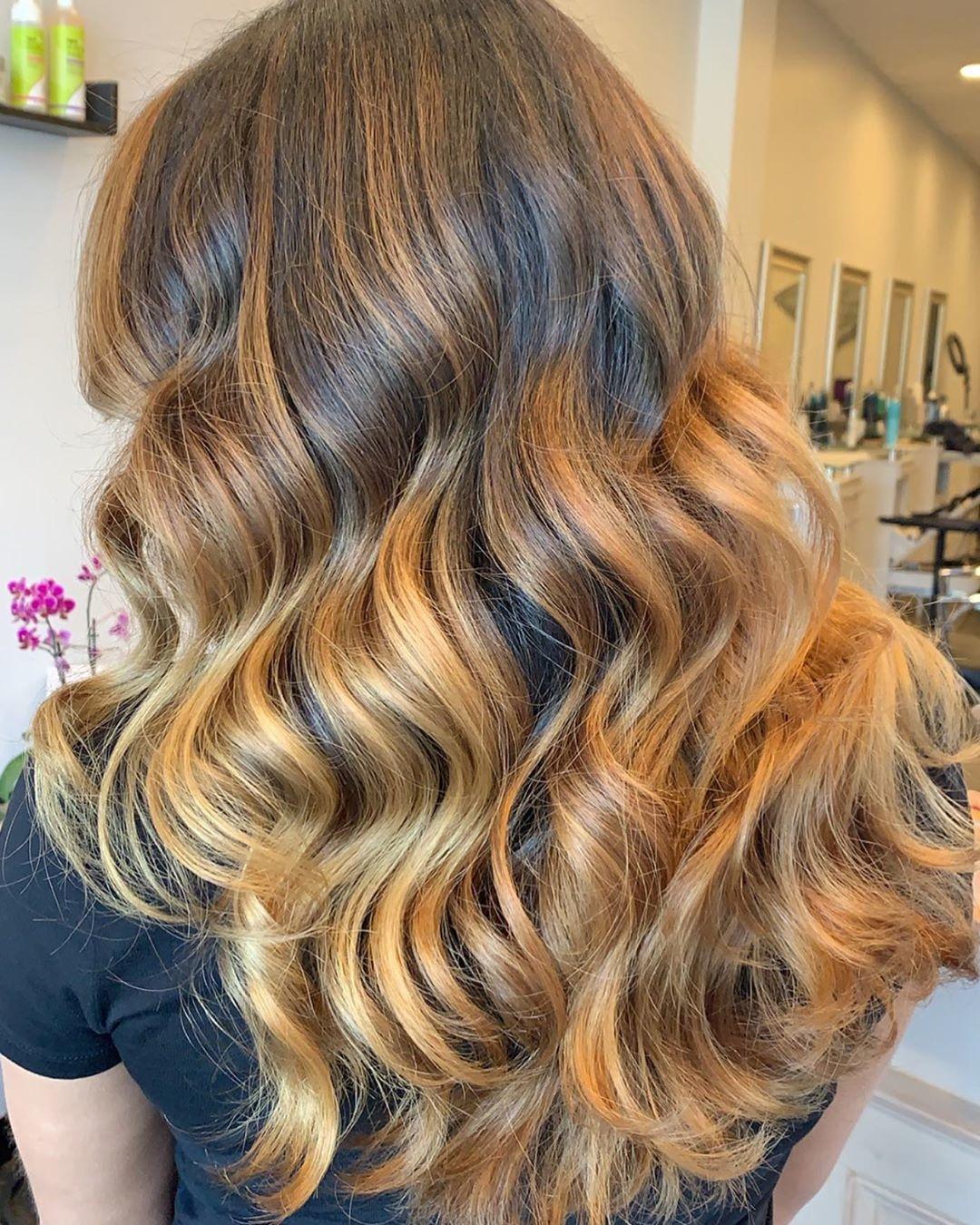 Femme avec des cheveux longs, ondulés, caramel et blond miel.