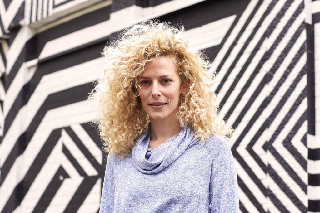 Image de face d'une femme aux cheveux bouclés, blond pâle, miel.