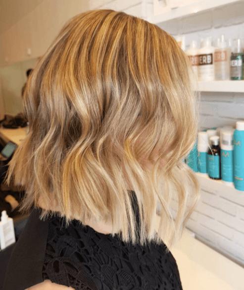 Vue de côté d'une femme dont les cheveux sont de couleur miel et ondulés.