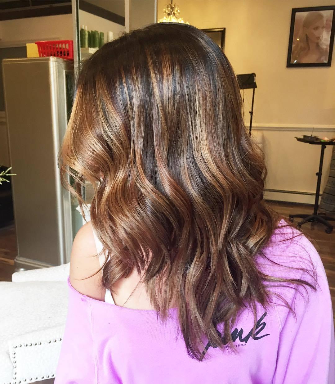 Femme avec des cheveux mi-longs ondulés de couleur châtain miel.