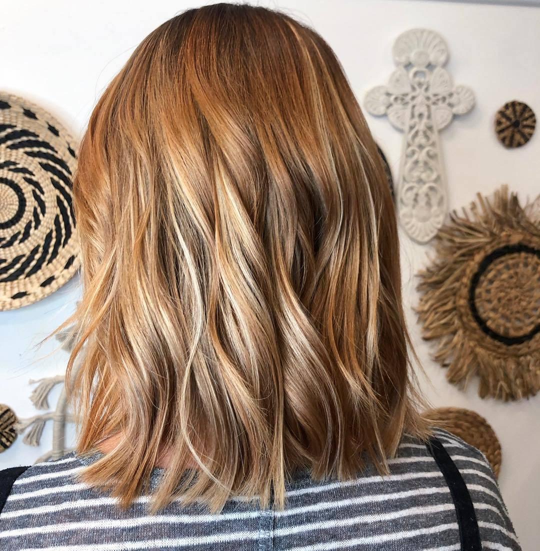 Femme avec une coupe de cheveux ondulée rouge miel clair