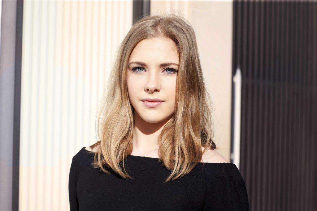 Image de face d'une femme aux cheveux mi-longs, blond miel