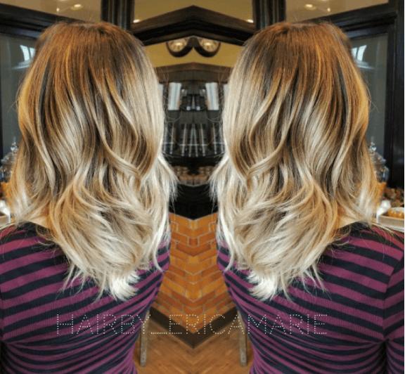 Vue arrière d'une femme avec des cheveux ondulés - racines foncées et cheveux blond miel.