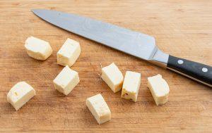 Cubes d'halloumi crus près d'un couteau