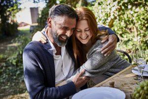 Un père heureux et sa fille adulte s'embrassant lors d'une garden-party.