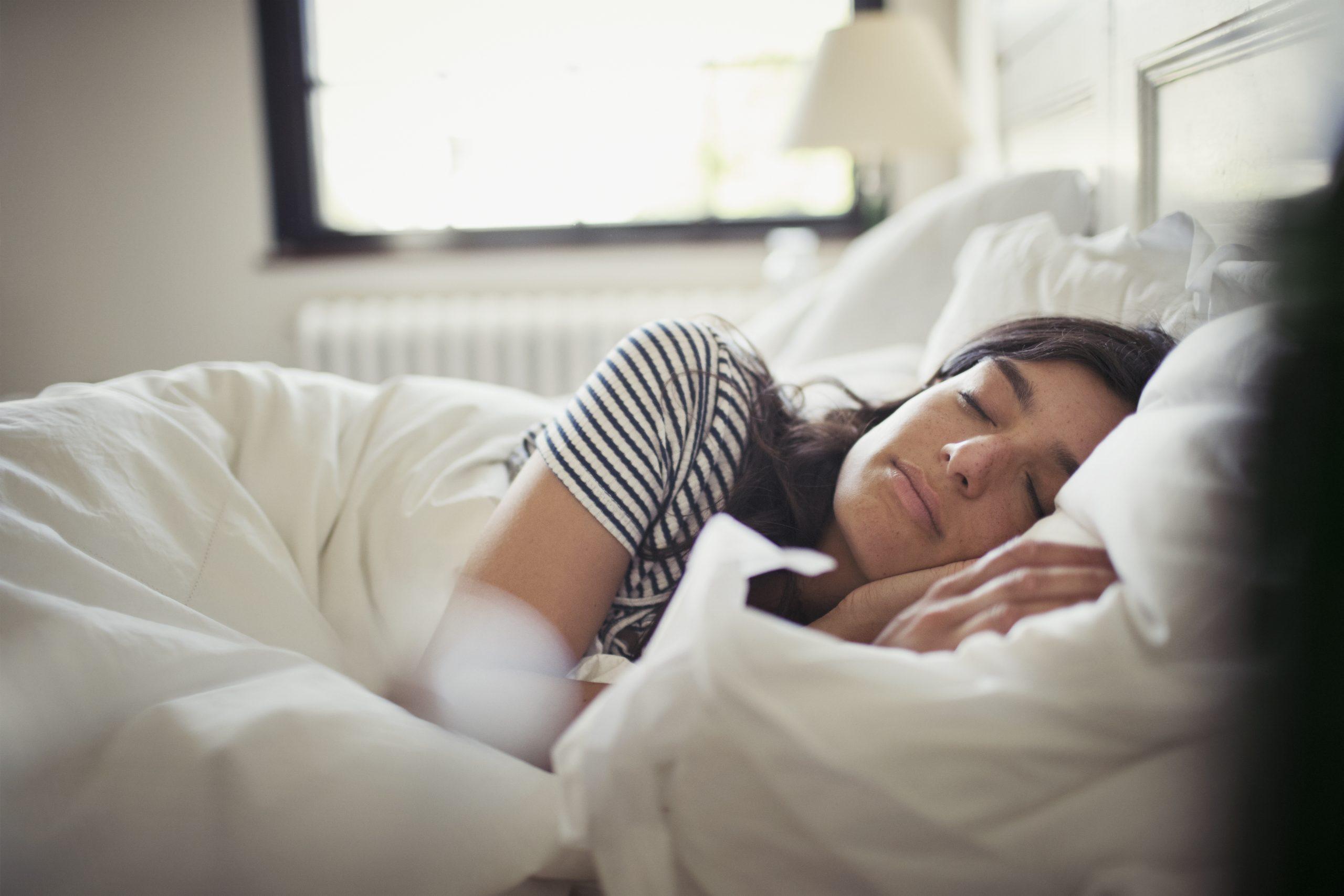 Une femme essayant de dormir dans un lit dans une pièce lumineuse