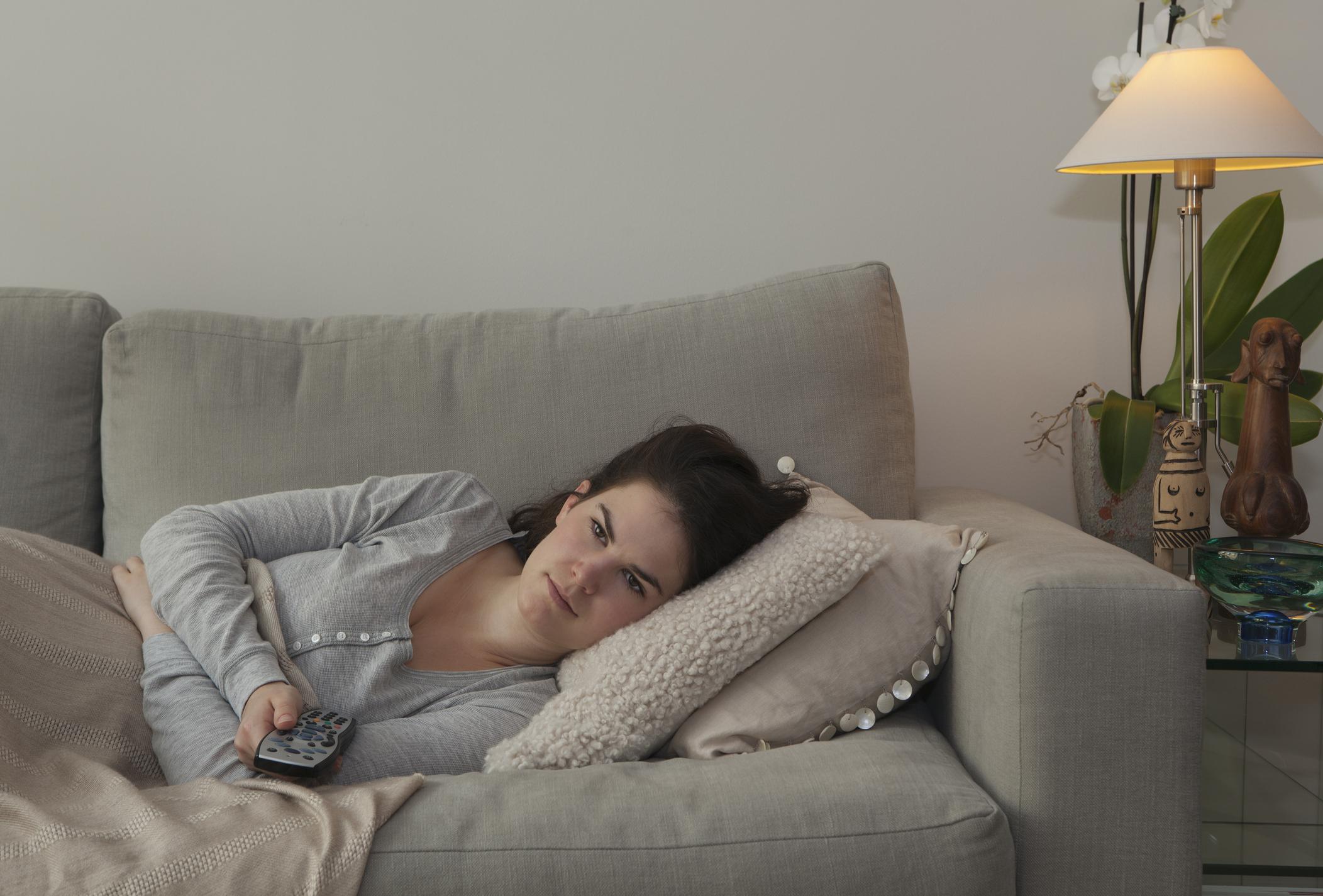 Jeune femme tenant la télécommande de la télévision