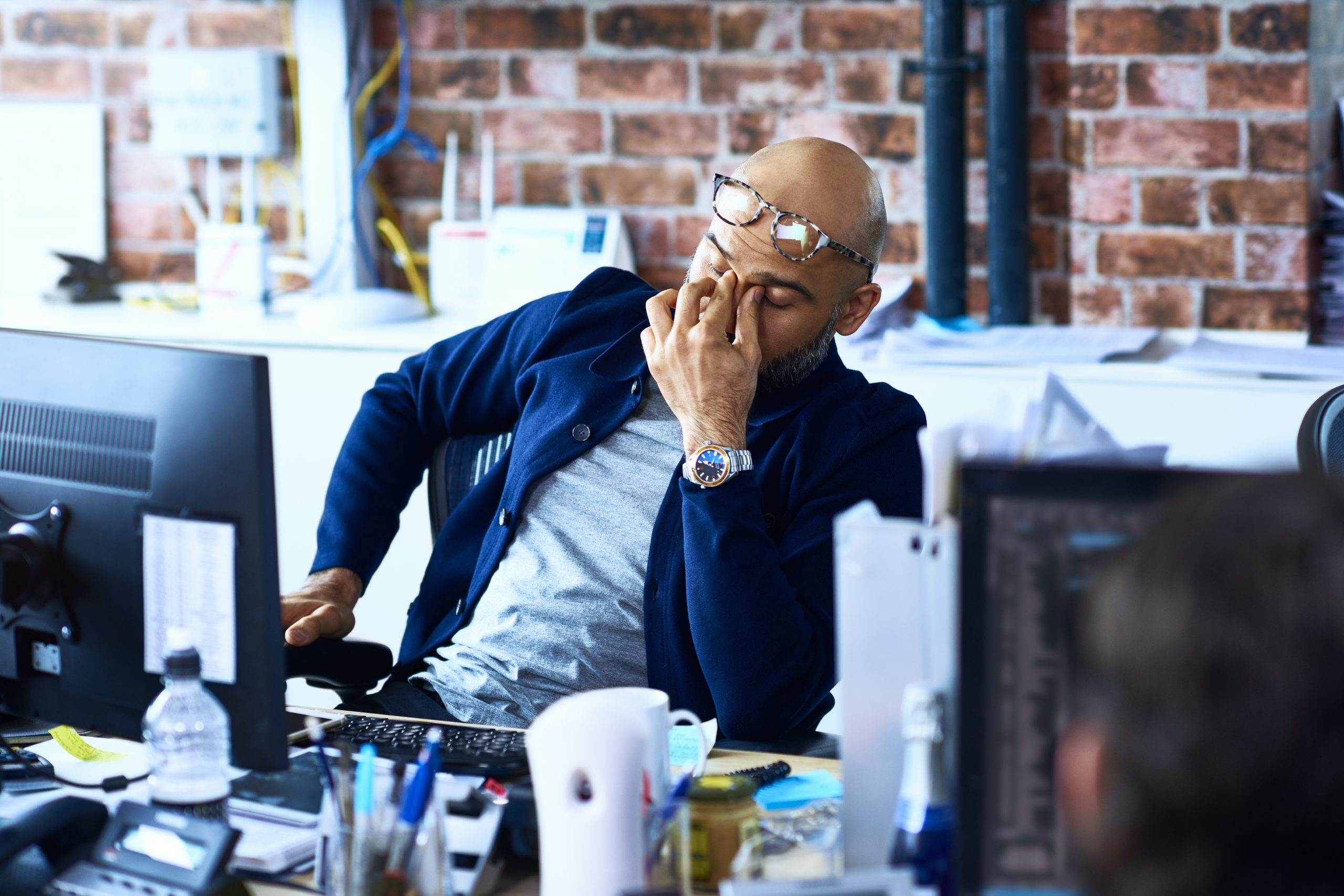 Un homme fatigué assis à son bureau au travail se demandant pourquoi je suis toujours fatigué ?