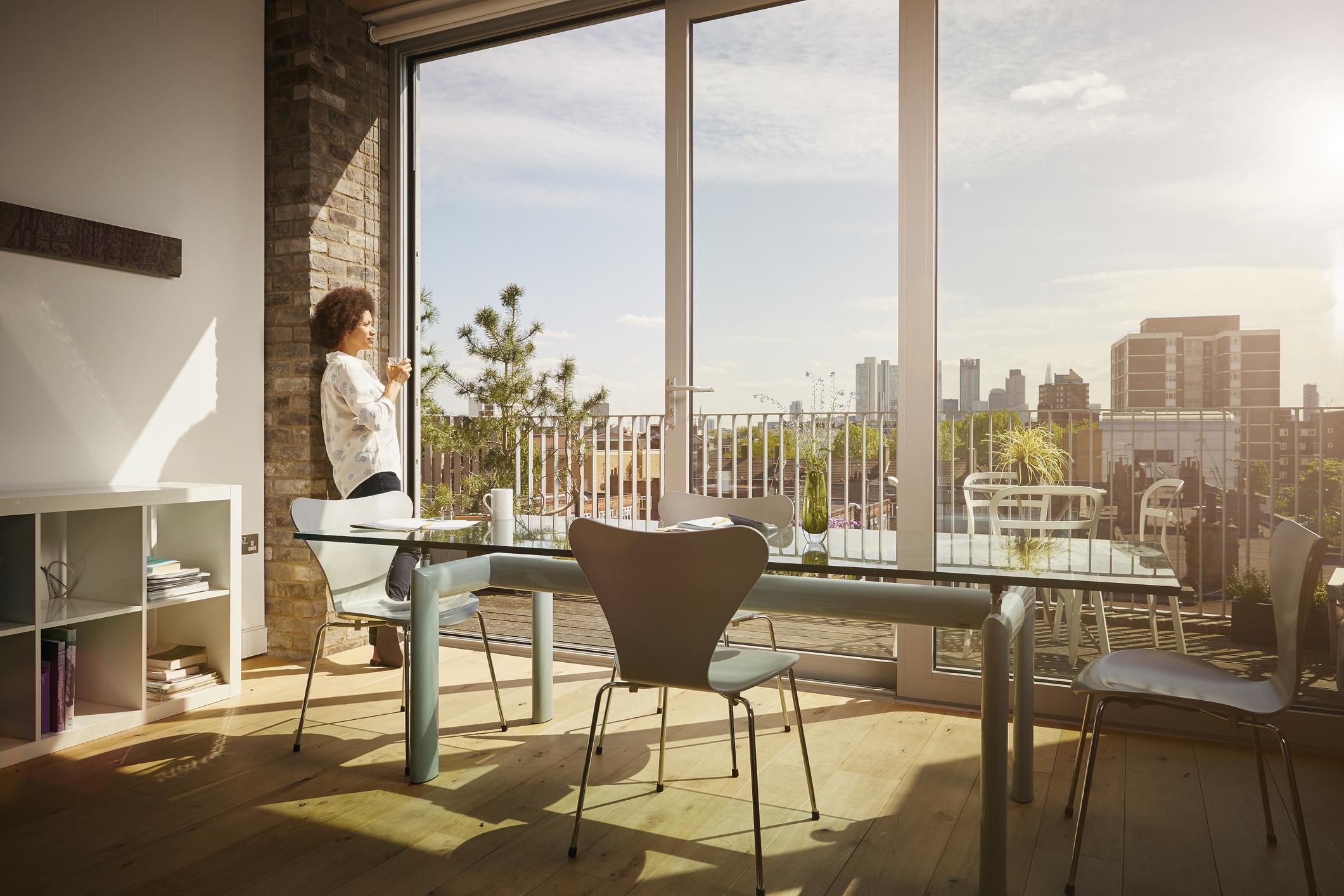 Femme regardant la vue par la fenêtre de son appartement.