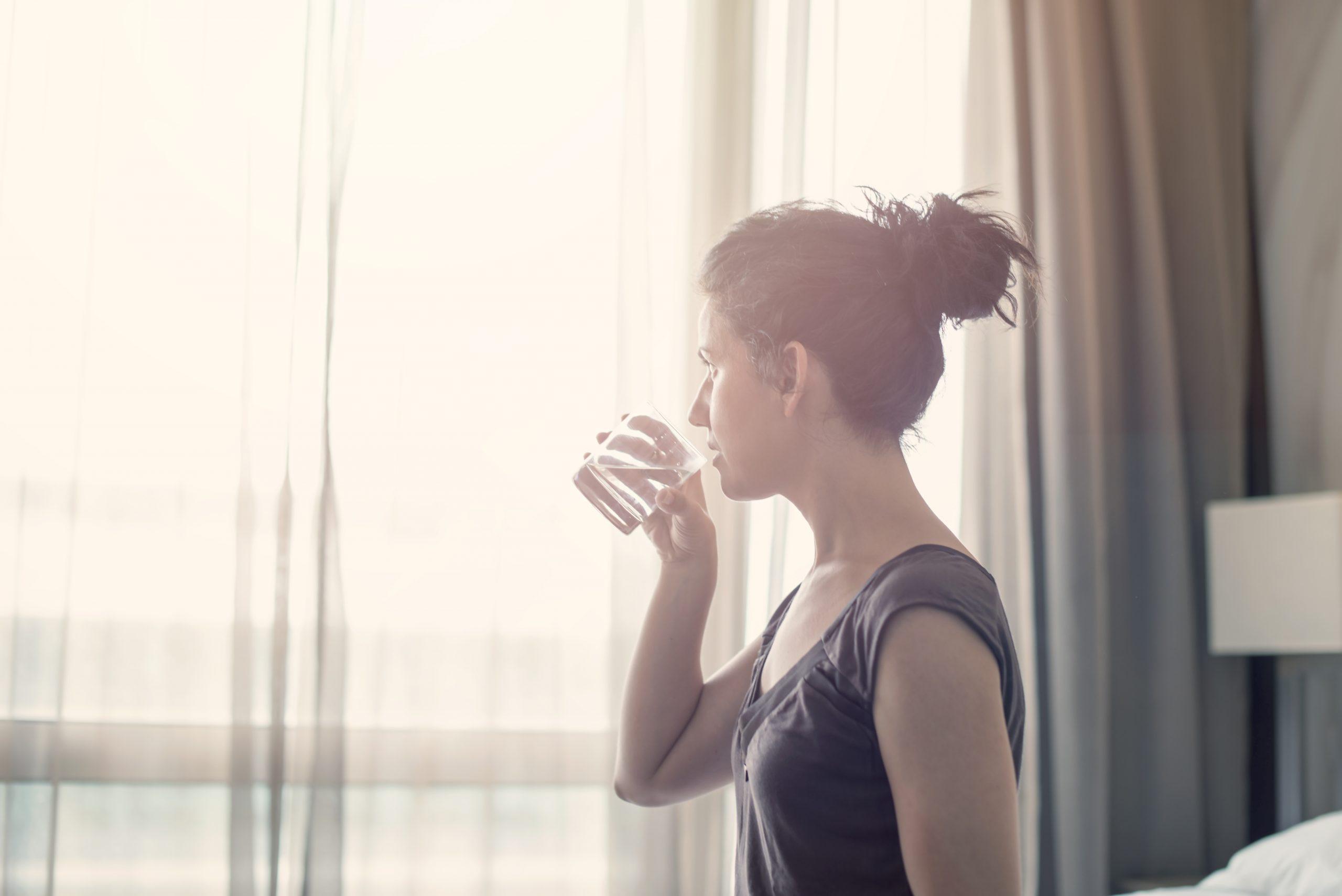 Une femme regarde par la fenêtre et boit un verre d'eau.