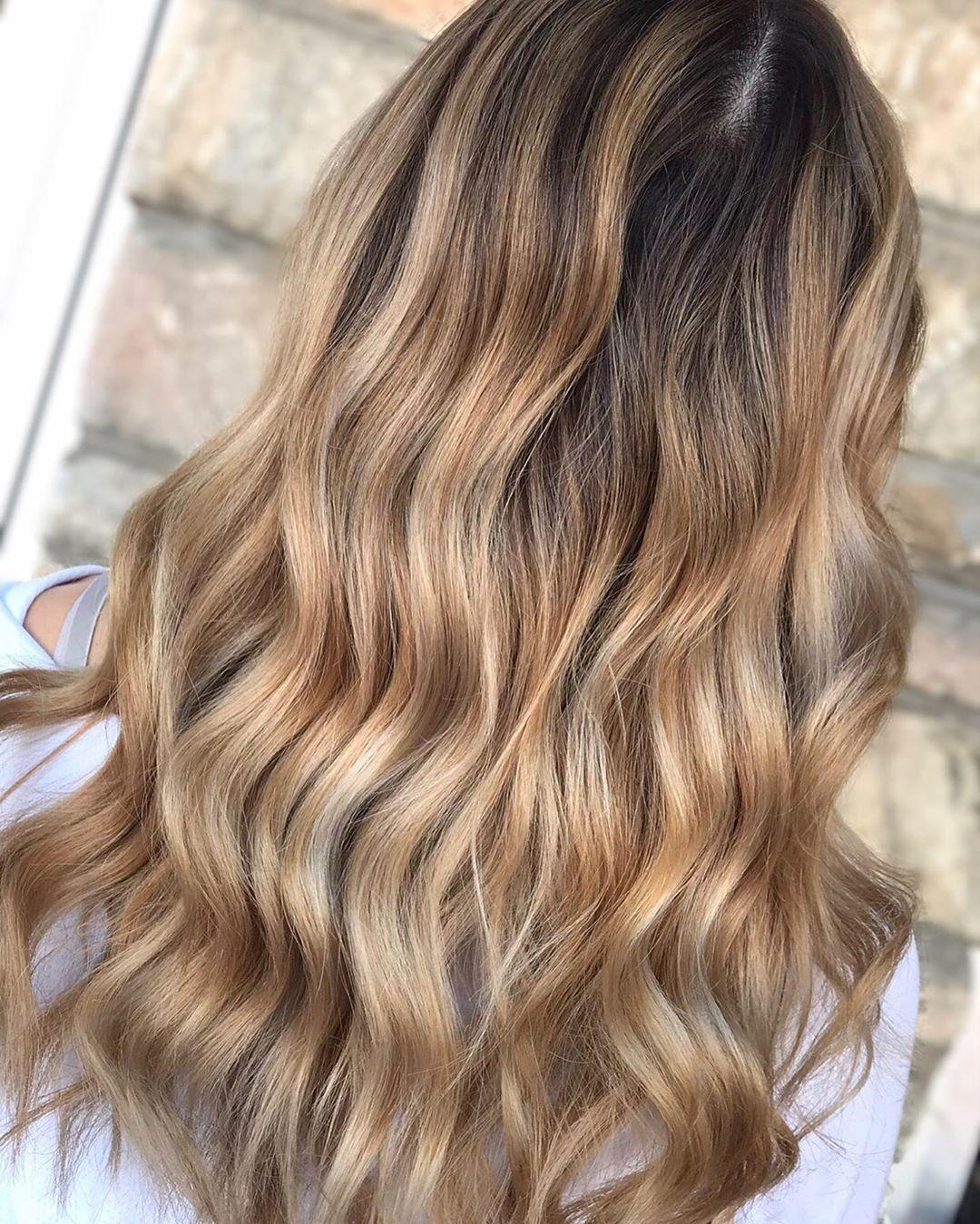 Femme avec de longs cheveux blond miel doré ondulés