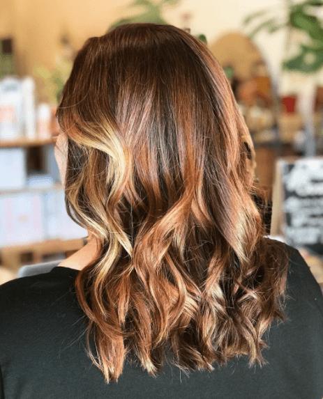image vue de côté d'une femme aux cheveux ondulés avec balayage dans des couleurs de cheveux blond miel