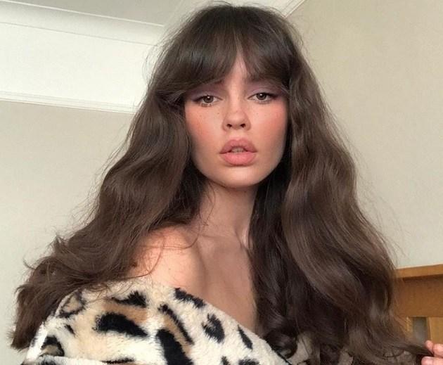 Types de franges : Femme aux longs cheveux châtains ondulés avec une frange Bardot, portant une veste à imprimé léopard.