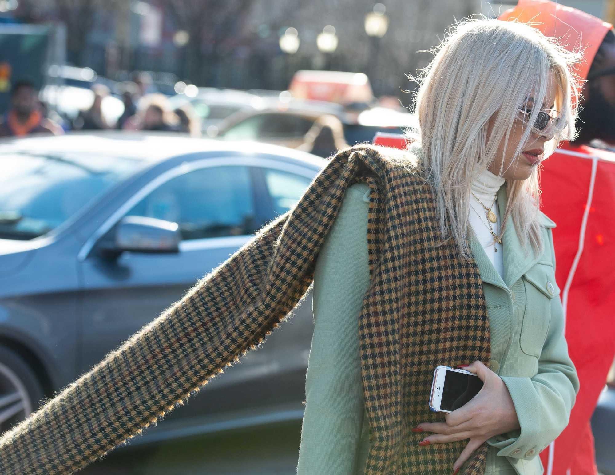 Femme dans la rue avec des cheveux blond cendré lisses aux épaules, portant un foulard à carreaux avec un blazer vert menthe à l'extérieur.