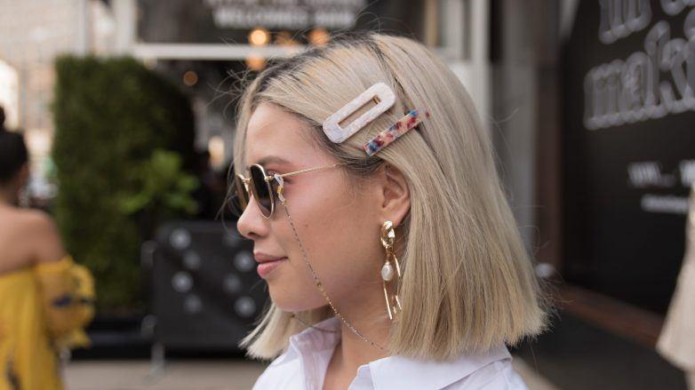 Femme avec une coupe longue blonde décolorée avec des pinces à cheveux.