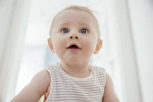 Un bébé garçon modèle curieux regardant vers le haut dans une lumière vive.