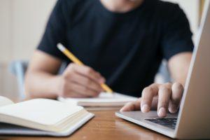 Un homme étudie pour ses reprises de GCSE avec un ordinateur portable et un bloc-notes.