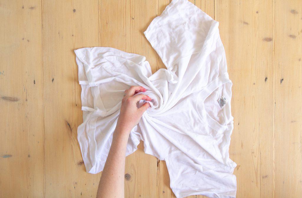 Un t-shirt tordu sur une table en bois.