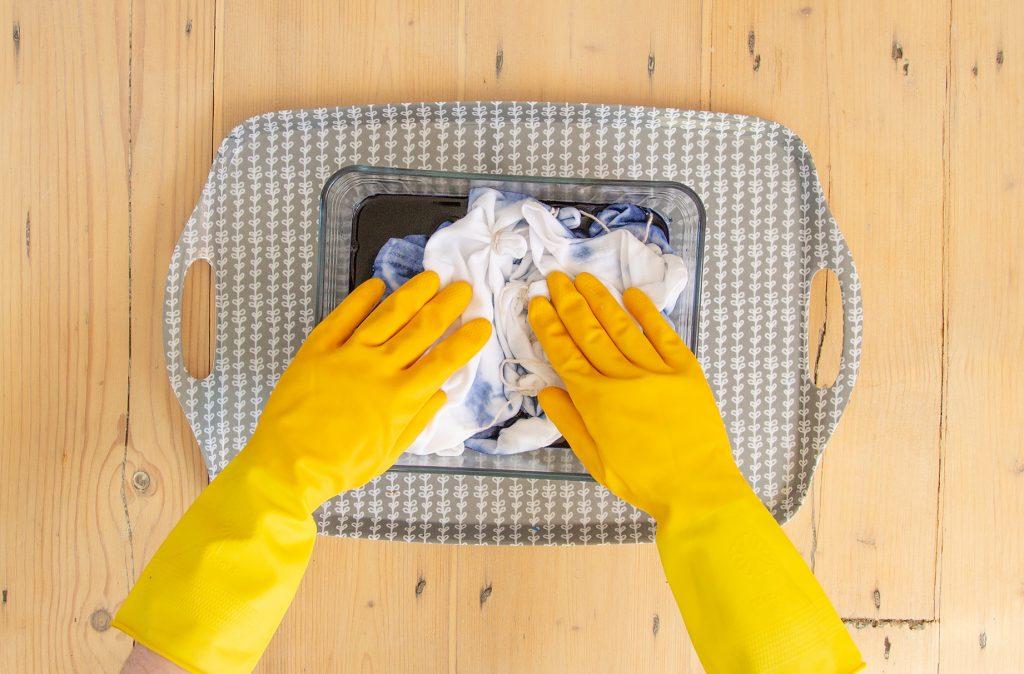 Quelqu'un avec des gants en caoutchouc remplissant un plat profond avec la teinture bleue.