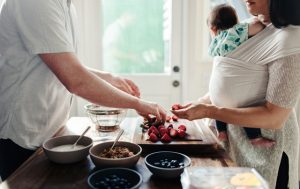Une femme et son bébé avec son partenaire pendant qu'ils préparent le repas.