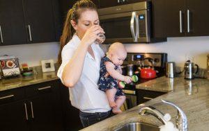 Une femme suivant un régime d'allaitement tient son bébé dans ses bras et boit de l'eau dans la cuisine.