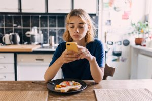 Jeune femme utilisant un téléphone pour appeler une banque alimentaire locale.