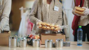 Femme emballant un colis alimentaire dans une banque alimentaire locale.