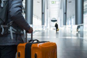 Un homme voyageant avec une valise alors que la liste verte est annoncée