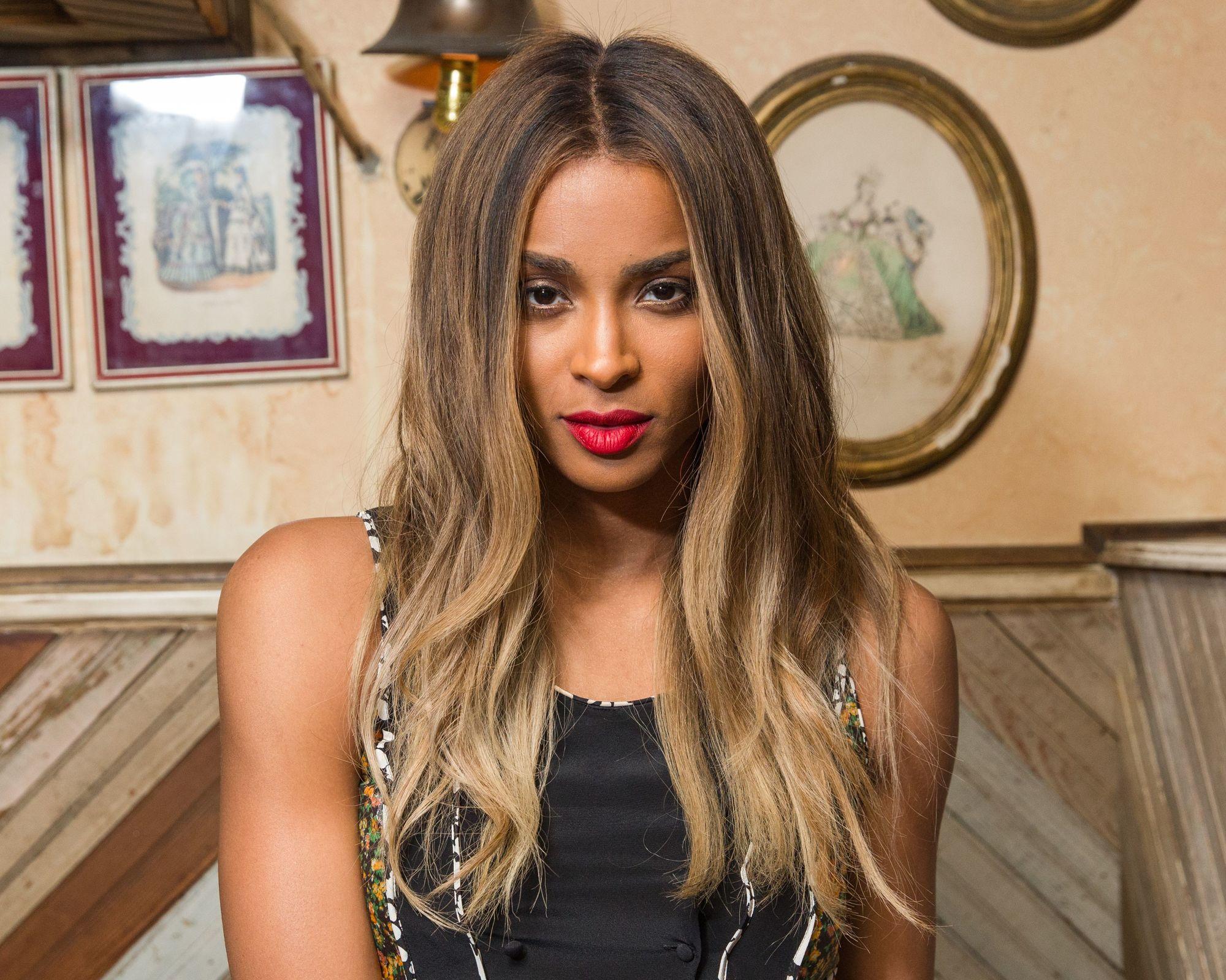 Ciara avec des cheveux bruns ondulés dans les coulisses d'un spectacle de coachs.