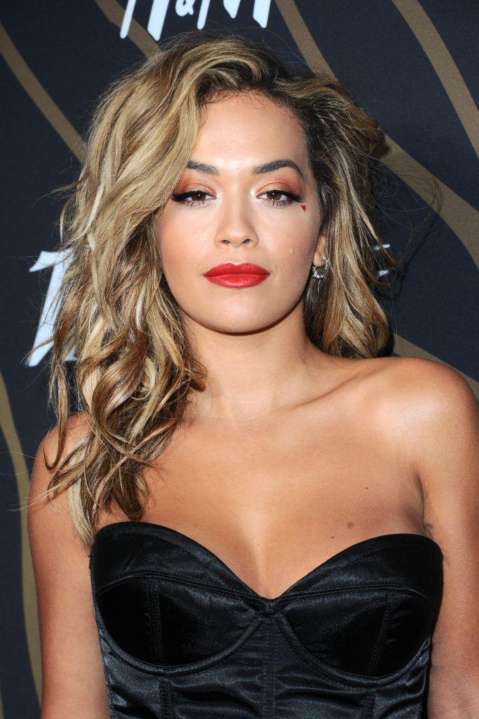 Rita Ora avec ses cheveux ondulés de couleur brune.