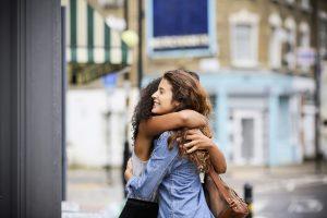 Deux femmes s'étreignent dans la rue, car les règles concernant les étreintes entre deux personnes ont changé.