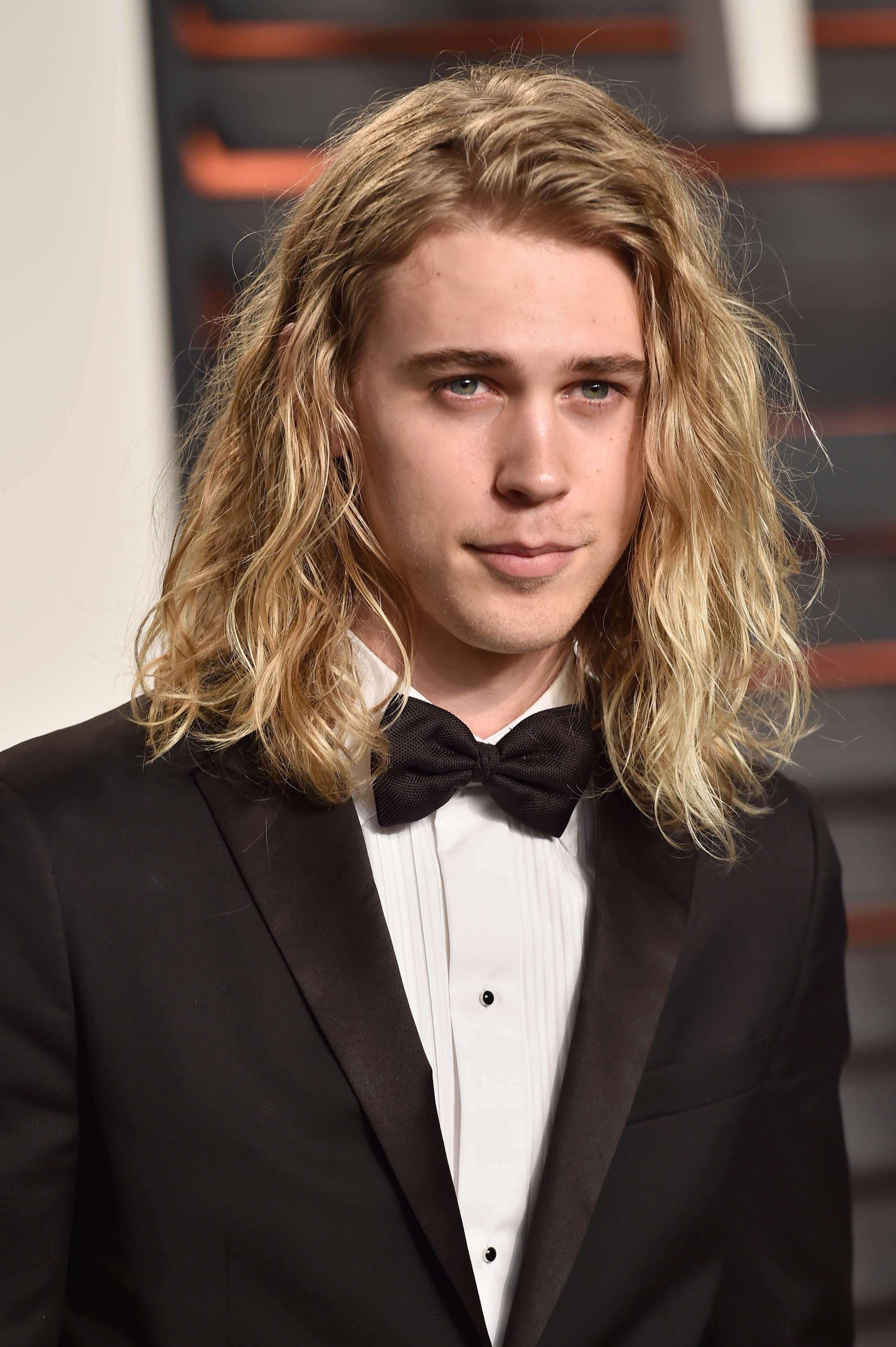 Austin Butler avec de longs cheveux blonds ondulés portant un smoking.