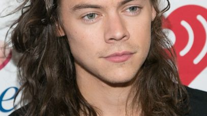 Red carpet shot of Harry Styles with long brown wavy hair pushed back and swept to one side