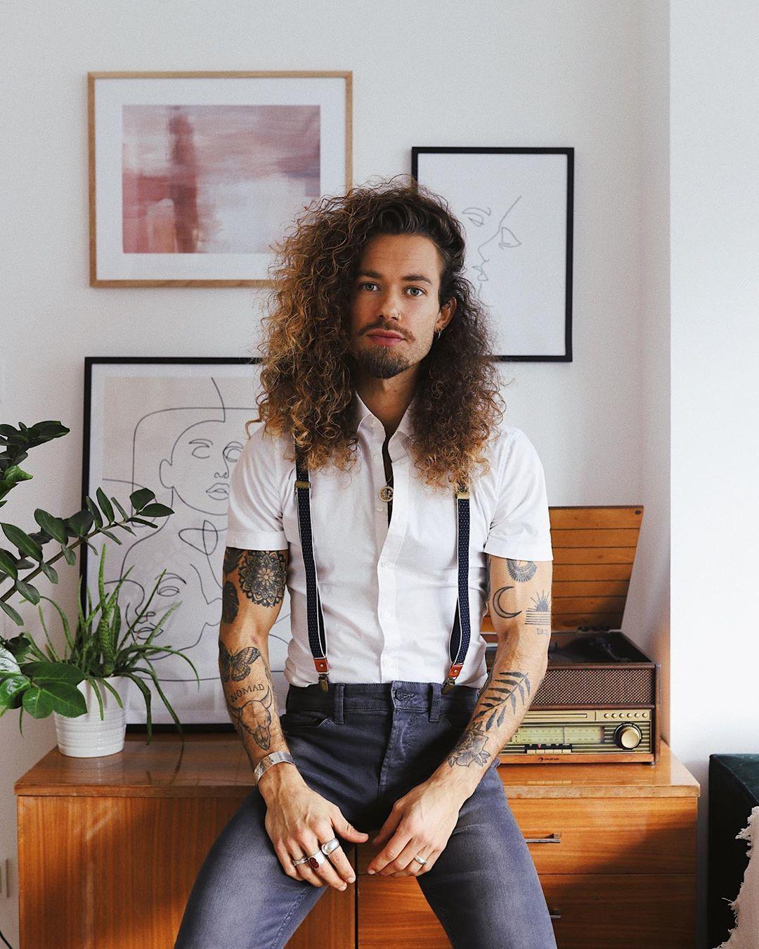 Homme avec des cheveux longs naturellement bouclés