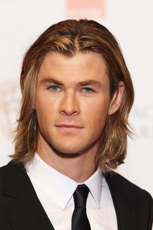 Chris Hemsworth avec de longs cheveux blonds séparés au milieu dans un style des années 90.