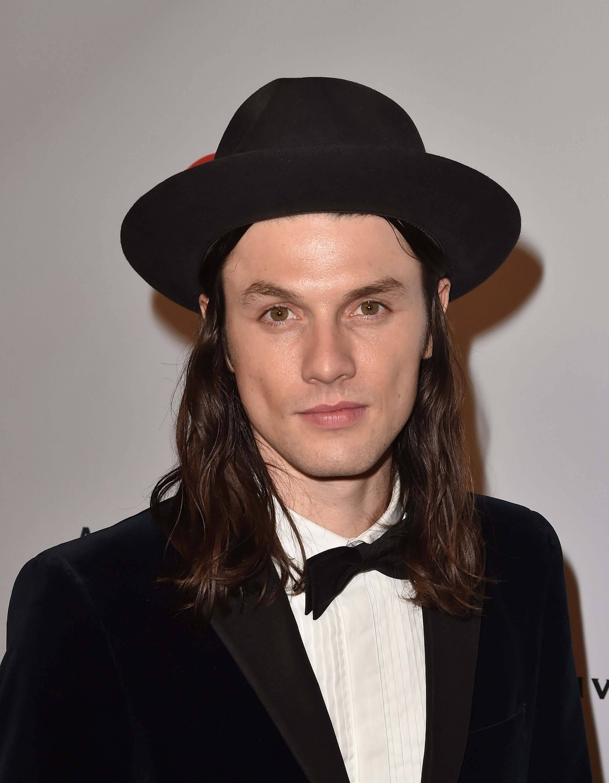 James Bay avec des cheveux bruns lisses aux épaules et un chapeau fedora noir, portant une tenue de cravate noire.