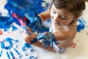Gros plan d'un enfant en bas âge qui fait des empreintes de mains.