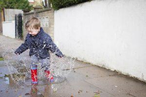 Un jeune enfant qui saute dans les flaques d'eau.