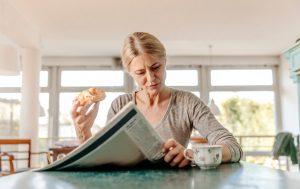 Femme mangeant une pâtisserie et buvant un café en lisant le journal.