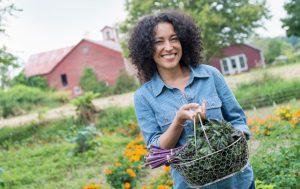 Une femme en train de jardiner tenant des feuilles vertes qui sont idéales pour un régime de ménopause.