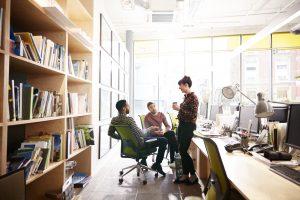 Des personnes se réunissent à l'intérieur sur leur lieu de travail, après un changement des règles concernant le nombre de personnes pouvant se réunir à l'extérieur et à l'intérieur.