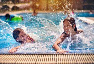 Des sœurs pataugeant dans une piscine dans l'un des nombreux parcs de caravanes qui rouvrent leurs portes.